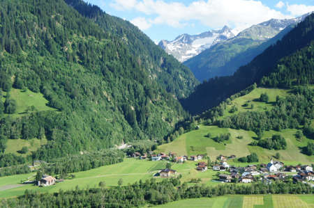 cloud capped: Mountain landscape with steep mountains and deep valleys, forested and snow-capped mountains, a mountain village in the valley, landscape in Graubunden in the Switzerland Stock Photo
