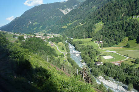anterior: View to the valley of the Anterior Rhine in Graubunden in Switzerland, forested mountains, meadows and villages and fields, blue sky with white clouds