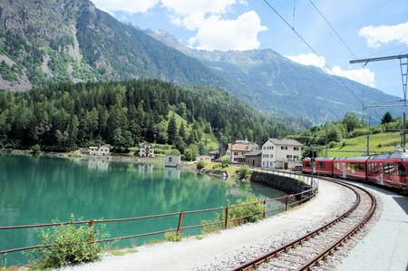 travelled: Travelled with the Bernina Railway in Grisons; the journey goes past the idyllic mountain lake Lago di Poschiavo; steep mountain hanging, blue sky and white clouds