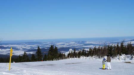 erzgebirge: View from the peak of the Fichtelberg on the snowy Erzgebirge, winter landscape in Saxony, blue sky