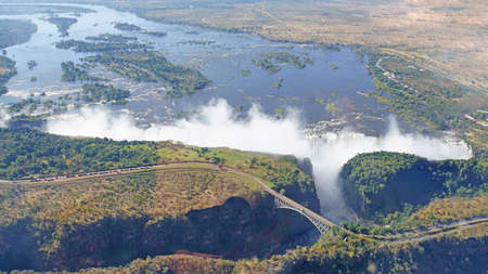 View from the air to the Victoria Falls, border bridge between Zambia and Zimbabwe over a canyon, Zambezi River with wooded islands Stock Photo