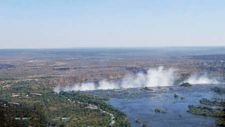 arial view: The Zambezi River in Zambia, de break-off edge and the spray of Victoria Falls, in the background a canyon landscape Stock Photo