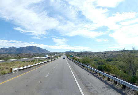 mountainous: Long-haired road in the desert in Arizona, United States of America, two-lane roadway with flag and emergency lane, mountainous landscape and blue sky with clouds,