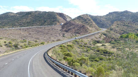 mountainous: Winding highway through mountainous desert landscape in Arizona, United States of America, two-lane roadway with marking and hard shoulder, blue sky with white clouds,