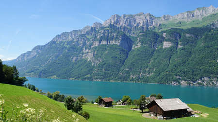View on the mountain lake Walensee in the Switzerland; Mountains, steep rock faces of the Churfirsten and turquoise-colored water; In the foreground a meadow with a farmhouse