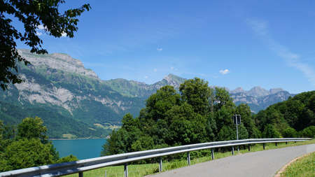 A parking lot at Lake Walensee in Switzerland, in the background of the steep rock faces of the Churfirsten Stock Photo