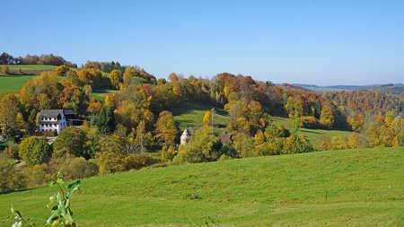 Das Erzgebirge im Herbst, hügelige Landschaft mit bunten Wäldern und  versteckten Häusern The Erzgebirge in autumn, hilly landscape with colorful forests and hidden houses