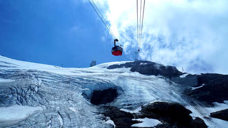 A cable car to the mount Titlis pass over the glacier, snowfields and rocks, blue sky and white clouds