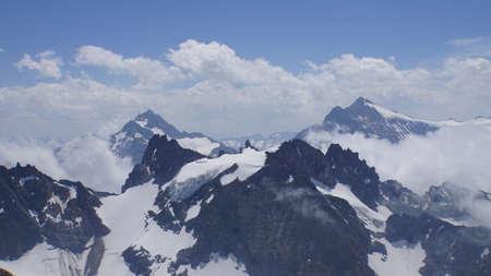 Bergwelt am Berg Titlis in der Schweiz, Bergspitzen und große Schneefelder, Berge teilweise in den Wolken Standard-Bild - 88694260