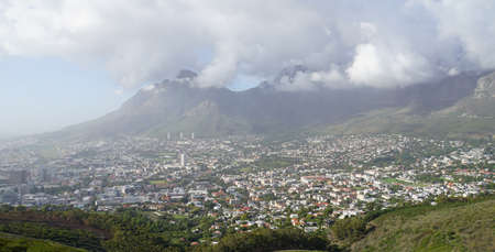 View to the sea of ??Cape Town houses, dense clouds around the Table Mountain