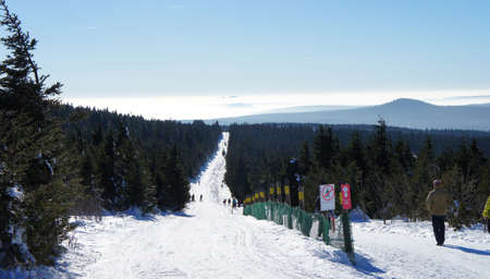 A cross country ski track through the woods on the Fichtelberg in the Ore Mountains, with a path for walkers, in the background of the mountain Auersberg in Western Ore Mountains Stock fotó