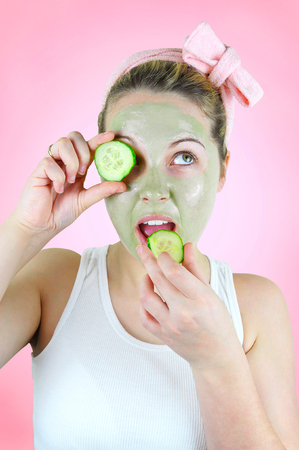 Young funny woman wearing a green facial mask and a pink headband is biting into a slice of cucumber on pink background.