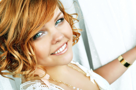 Close-up portrait of a happy smiling beautiful young woman with short curly red hair and bright blue eyes standing by the window between white lace curtains. Stock Photo