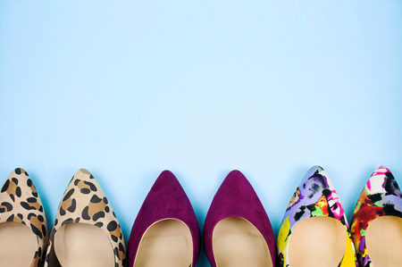 Stiletto shoes in different colours and patterns in one straight line on light blue background.