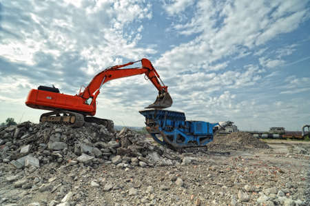Demolition construction site. Crawler excavator and stone breaker machinery working on demolition site.