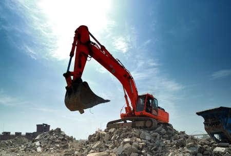 Demolition construction site details. Big crawler excavator at work on demolition construction site in daytime.