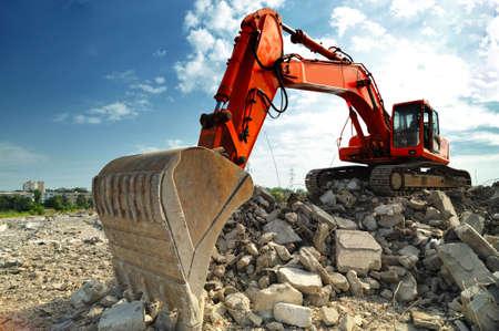 Crawler excavator on demolition site. Front view of a big crawler excavator working on demolition site. 写真素材