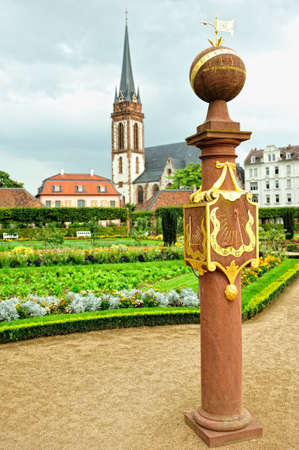 Measuring the time. Vintage old clock located inside Prince Georg garden with St Elisabeth catholic church in the background in city of Darmstadt, Germany. Stock Photo
