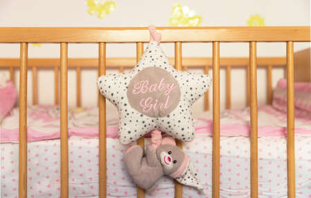 Newborns bed accessories. Sponge cushion in star shape attached from a newborn wooden bed.