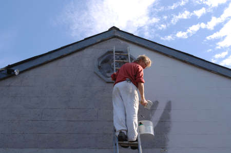 Painter against clear blue sky