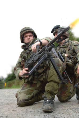 Soldiers firing machine gun