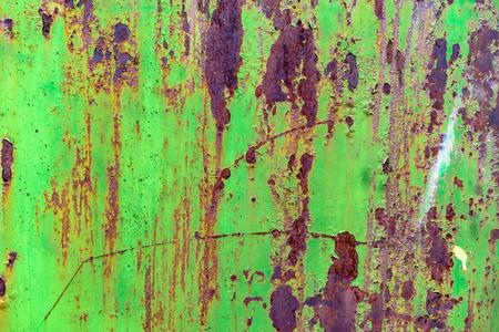 緑の塗装、古い、金属、錆びたドアの詳細。緑の錆びた金属のグリッジテクスチャーと傷