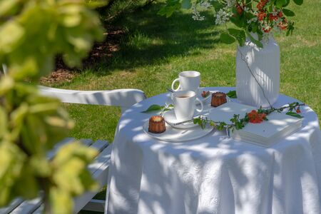 Enjoying coffee time on a sunny spring day. Served table with coffee, canele and flowers in the garden. There is a white wooden bench next to it