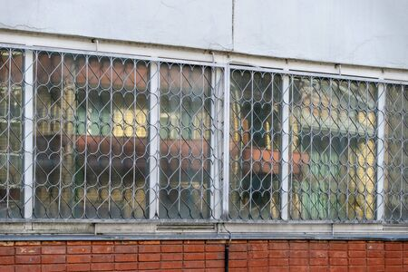 Metal decorative security grille on window with repetitive heart-shaped and a detail of old crumbled cracked plastered wall Stock fotó