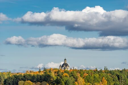 The dome of Church of the Visitation in the monastery of Pa?aislis in Kaunas on a sunny autumn day. View from far away, from behind Kaunas lagoon from the dam