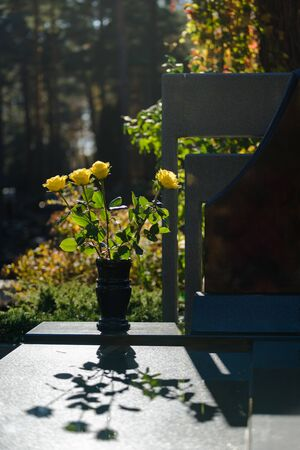 Yellow roses in vase to honor the dead on the grave against a light sunny autumn day and their shadows in Vilnius, Lithuania Foto de archivo