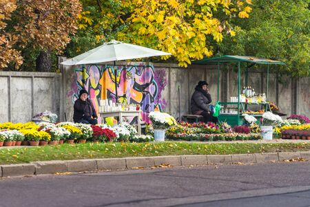 VILNIUS, LITHUANIA - OCTOBER 24 2017: Flower and candle trade at the entrance to the cemetery near the fence before All Saints' Day. Saleswomen are waiting for customers and talking on the phone. Standard-Bild - 143814788