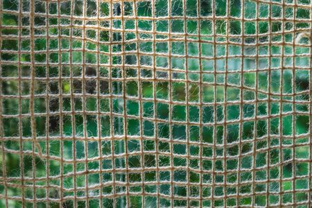 Cotton net of thick yarn outdoor. The mesh is against light. The background - a green meadow