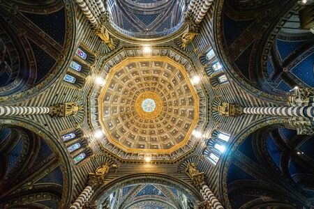 SIENA, ITALY - April 13, 2017: Interior of the  medieval Cathedral dedicated to the Assumption of Mary on a sunny day in Tuscany. Dome and ceiling with paintings, sculptures and stained glass windows