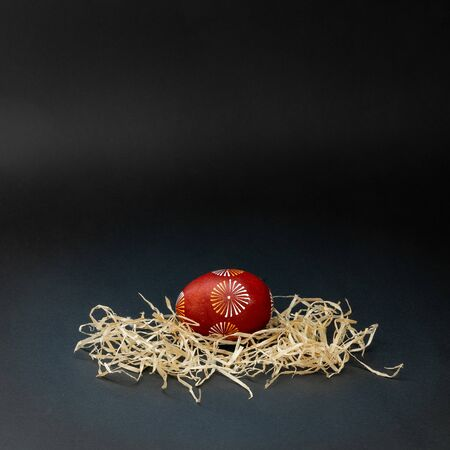 One traditional lithuanian Easter egg, lithuanian is called margutis, natural painting  red, white and yellow with bees wax in the nest. With copy space for text, isolated on black background