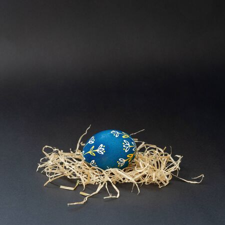 A blue Easter egg decorated in white and orange plant patterns using beeswax according to Lithuanian traditions. It is in the nest on a dark background. Place for text, close up