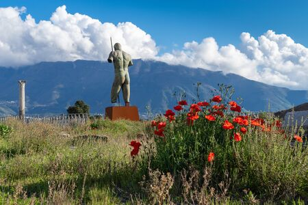 View from the ruins of the city of Pompeii to the mountains and clouds on a clear evening in spring, Italy. In the center is a sculpture Daedalus by sculptor Igor Mitoraj.Red poppies bloom next to it