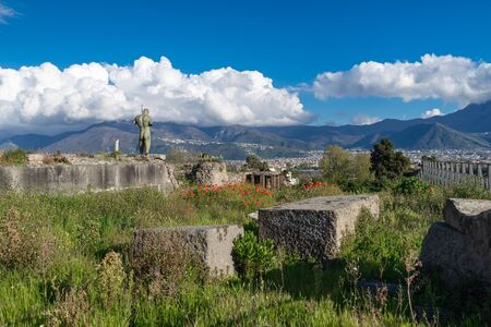 Landscape with the ruins of Pompeii in Italy, red poppies, mountains, blue sky, white clouds. The bronze sculpture Daedalus created by a sculptor of Polish origin Igor Mitoraj.Antique culture concept