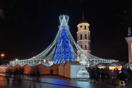 The most beautiful Christmas tree for Christmas 2019 and New Year 2020 in Europe is in Vilnius Cathedral Square, Lithuania. Stunning Christmas tree is depicted as a chess queen, and a lot of people on Christmas market. Long Exposure