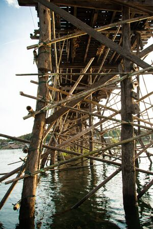 Wooden pillars of the bridge mon Songkalia river, Sangkhlaburi Kanchanaburi, Thailand photo