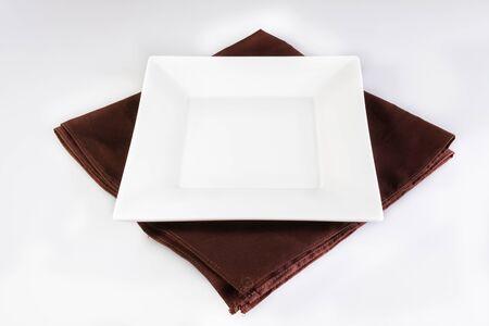 place mat: An empty plate on brown plate mat