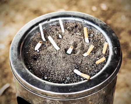 Cigarette in sand ashtray bin photo