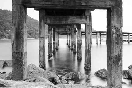pillar: Pillars of the Harbour Bridge  Black and white photo shows the old pillars and the movement of water  Stock Photo