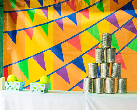 knockdown: The pyramids of tin cans for throwing balls at them on bunting background