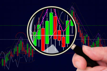 geld: Hand holding magnifying glass in front of chart Stock Photo