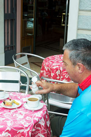 Senior cyclist recovers with coffee and cake Banco de Imagens