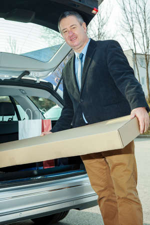 Man invites package in the car Stock Photo