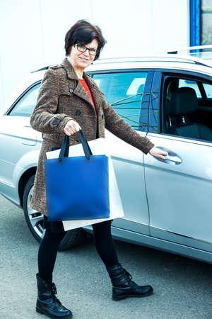 Woman with shopping bags next car Reklamní fotografie