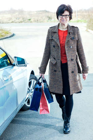 Woman with shopping bags next car Stock Photo