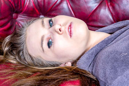 Woman is lying on the sofa and looks expressionless Stock Photo