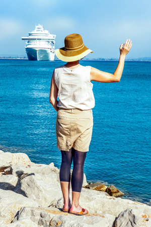 Woman with hat stands on the sea and waves, a cruise ship Stock Photo